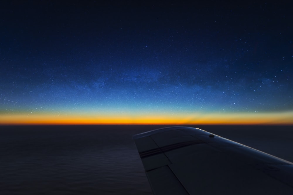 airplane wing over the blue sky during sunset