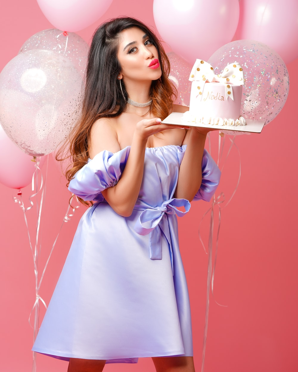 woman in pink dress holding white and pink happy birthday cake