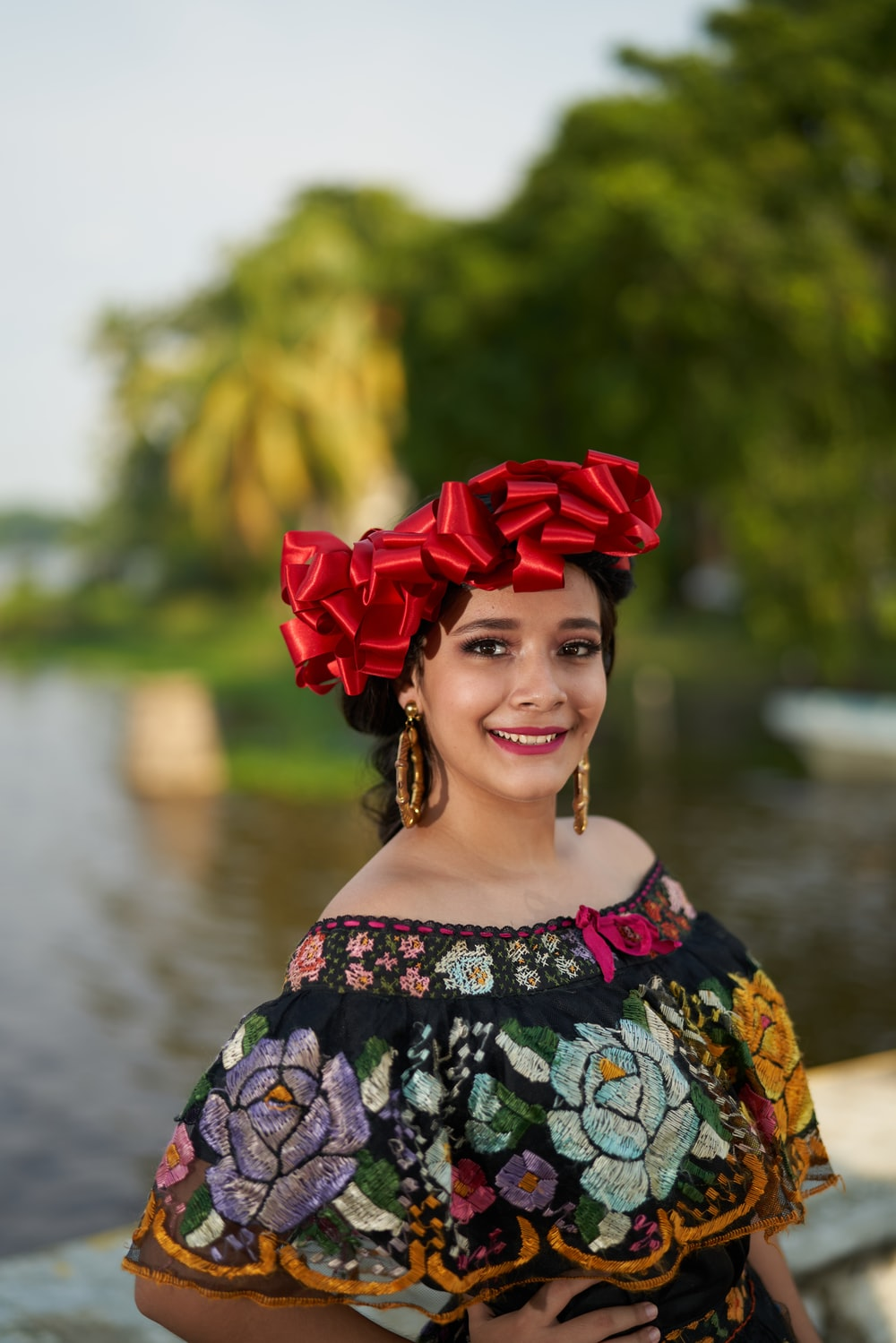 woman in blue and white floral off shoulder dress with red flower on head
