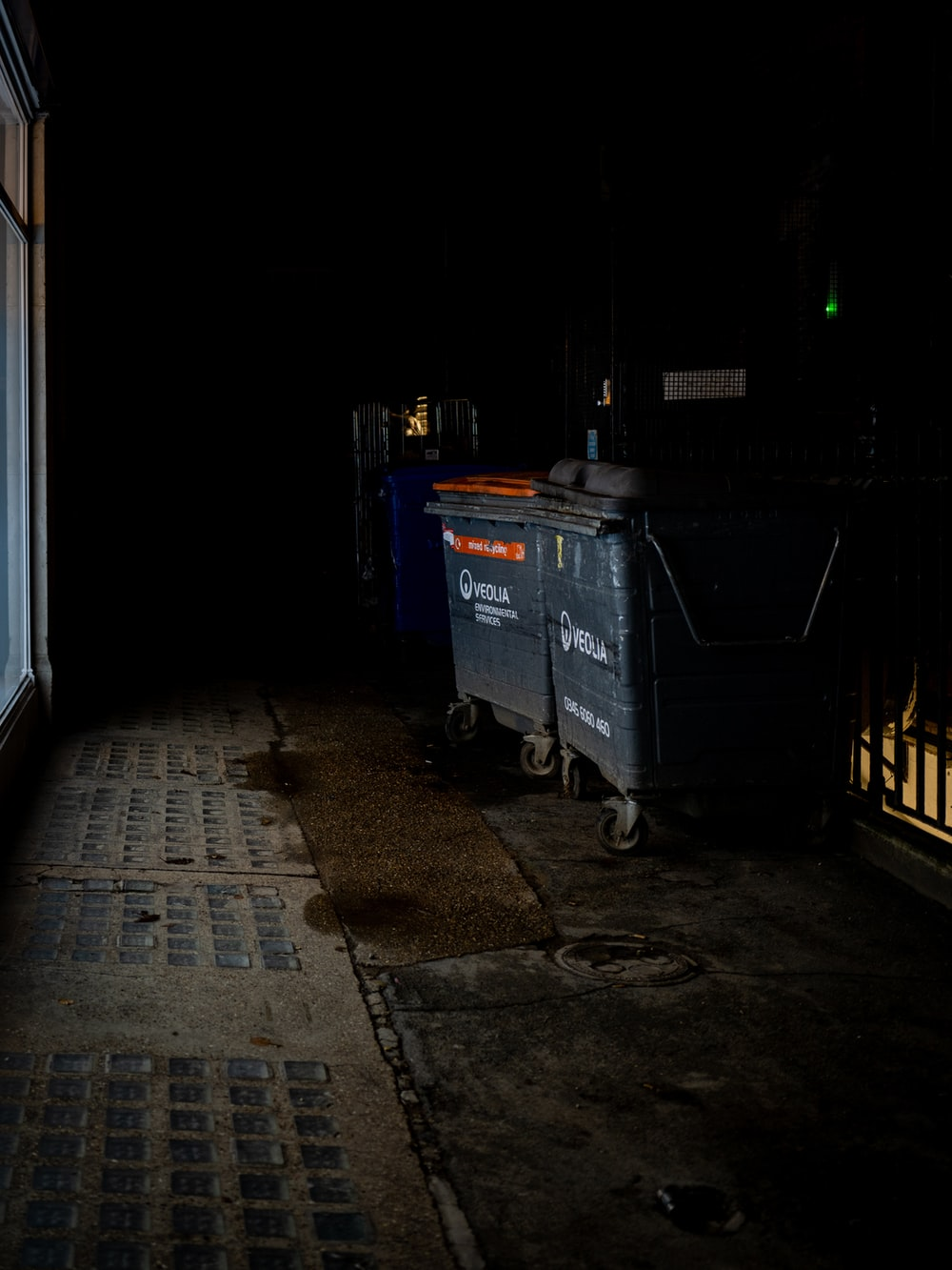 blue plastic trash bin beside white wall