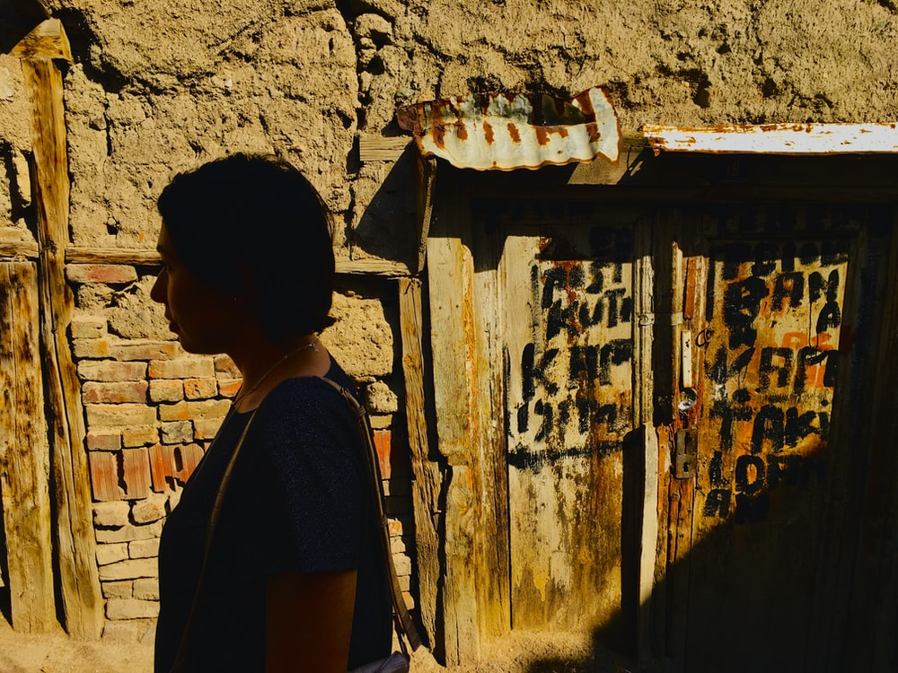 woman in black shirt standing in front of brown concrete wall