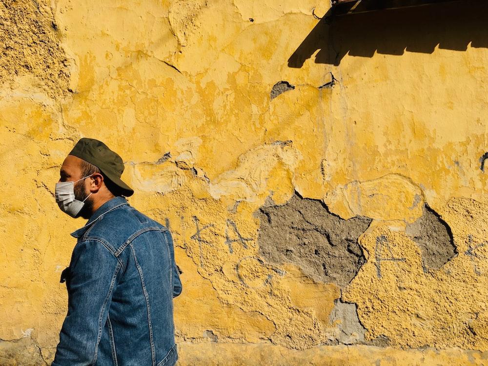 man in blue denim jacket and black cap standing beside brown wall