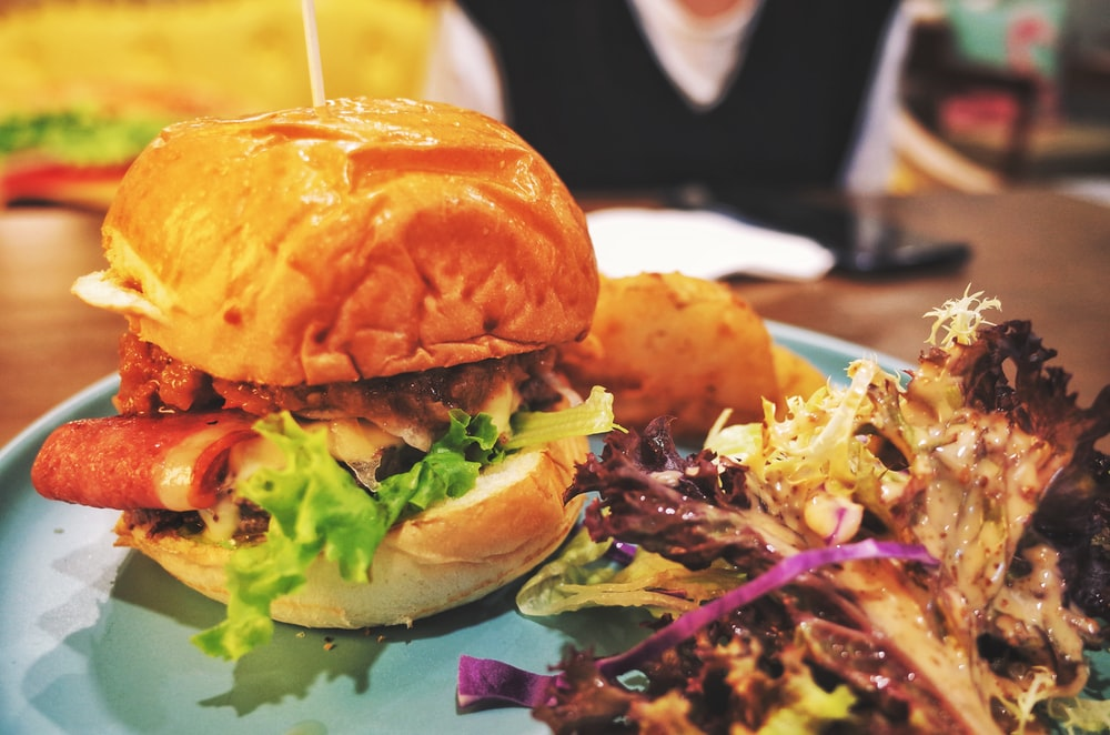 burger with lettuce and tomato on green plate