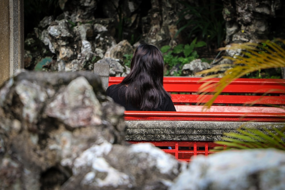 woman in black long sleeve shirt sitting on red bench