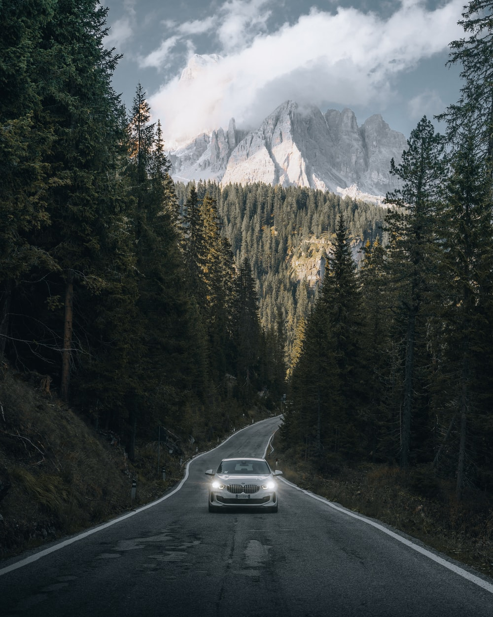 black car on road near green trees and snow covered mountain during daytime