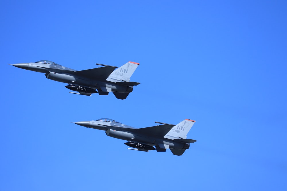 two fighter planes flying in the sky during daytime