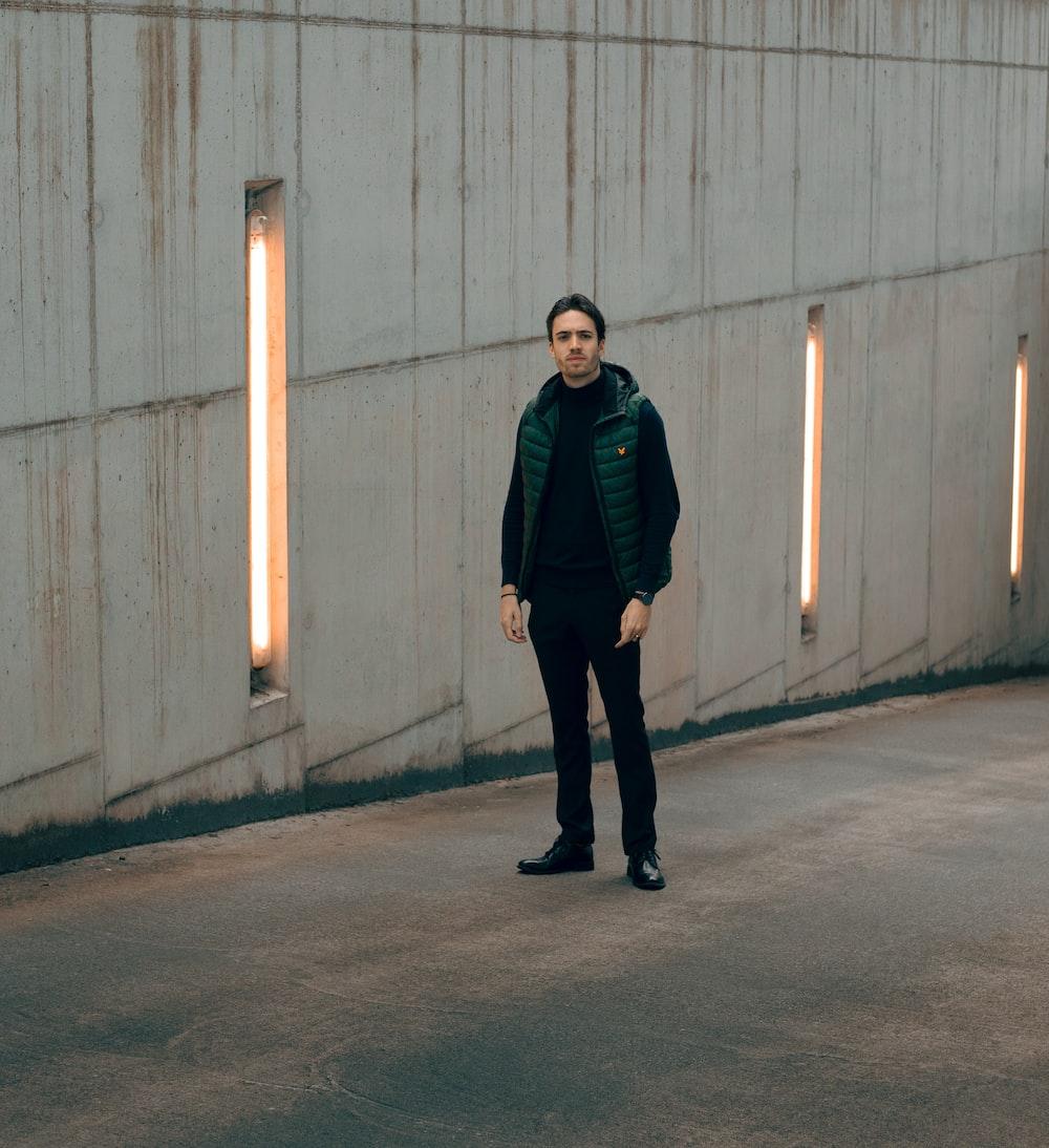 man in black jacket standing on gray concrete floor