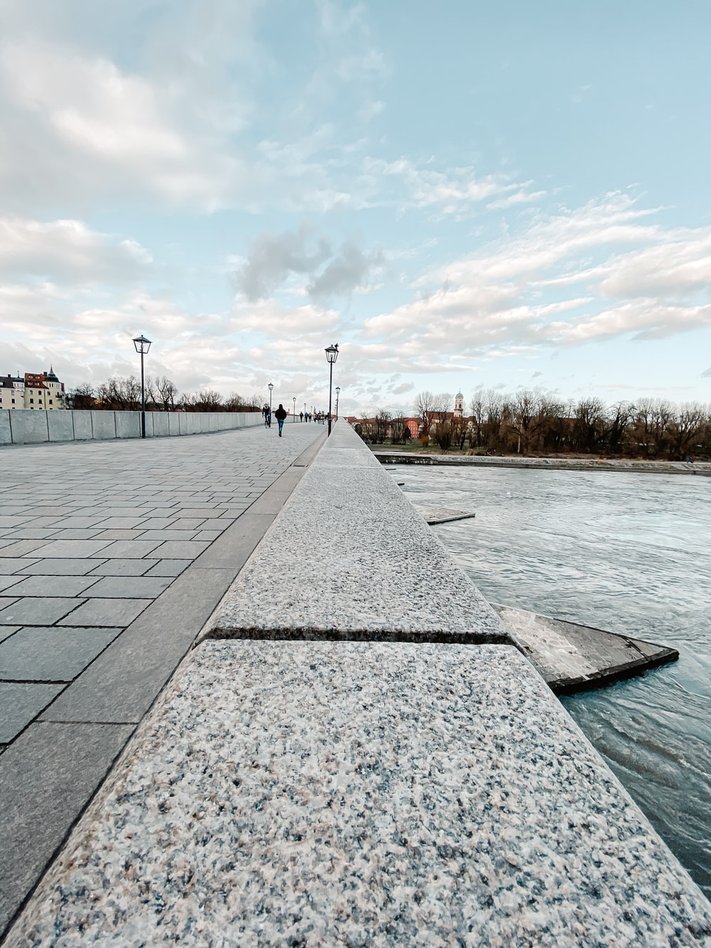 people walking on gray concrete pathway near body of water during daytime