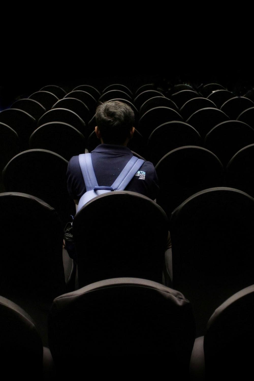 man in blue shirt sitting on black chair