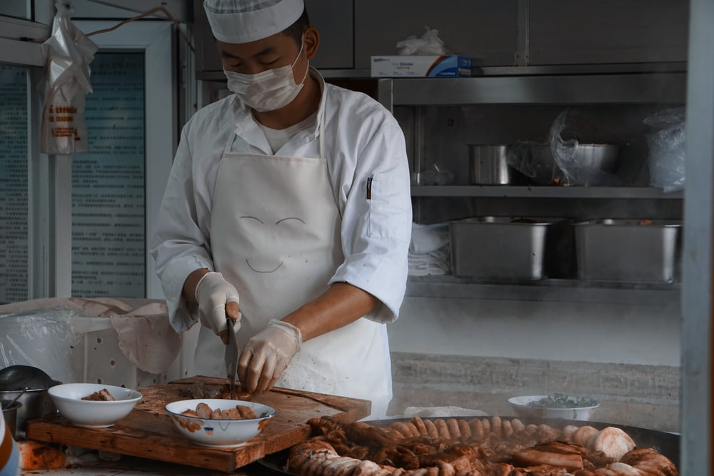 chef holding knife slicing meat