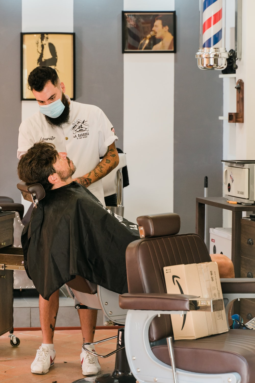 man in white t-shirt sitting on barber chair