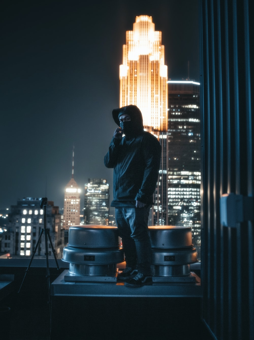 man in black jacket and blue denim jeans standing on black metal stand during night time