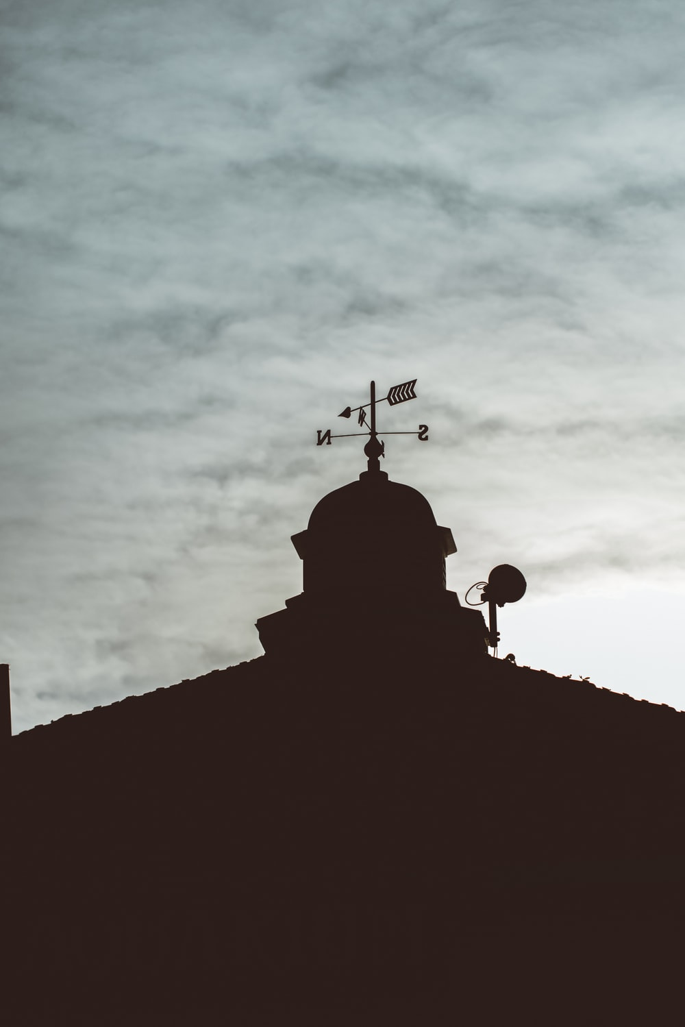 silhouette of cross on top of building