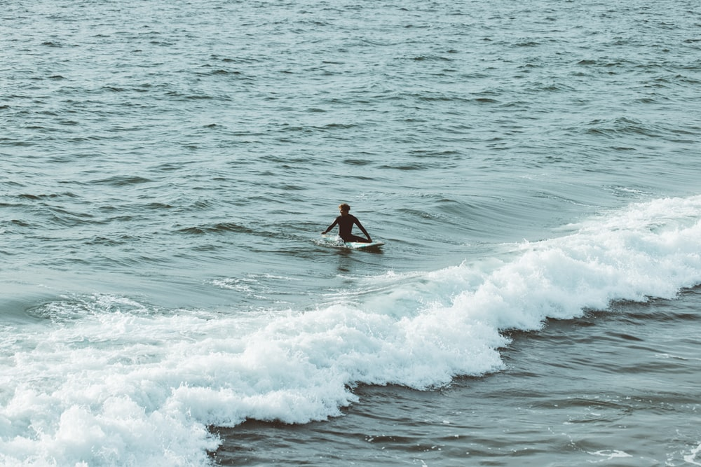 man surfing on sea waves during daytime