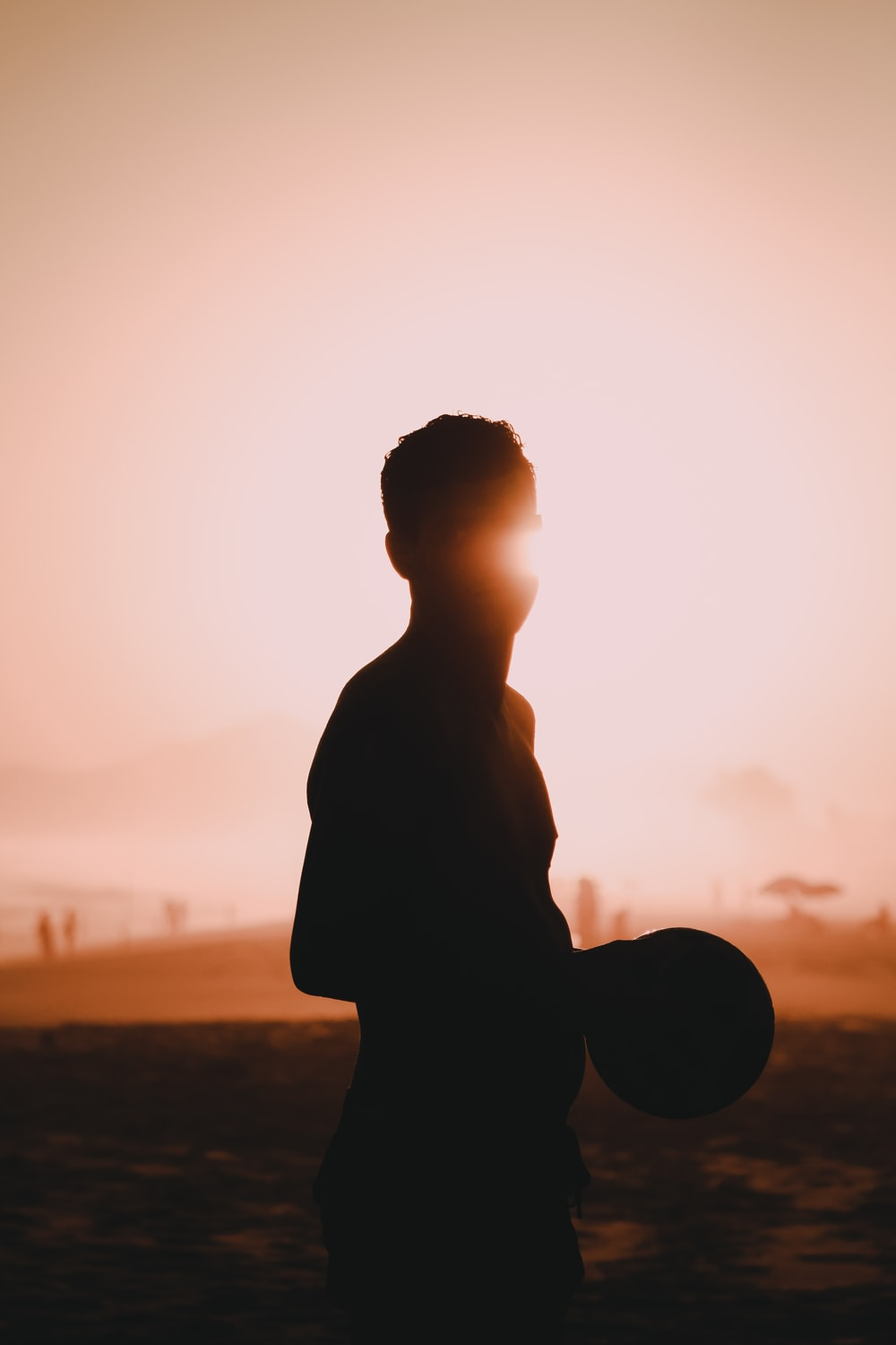 silhouette of man standing on field during sunset
