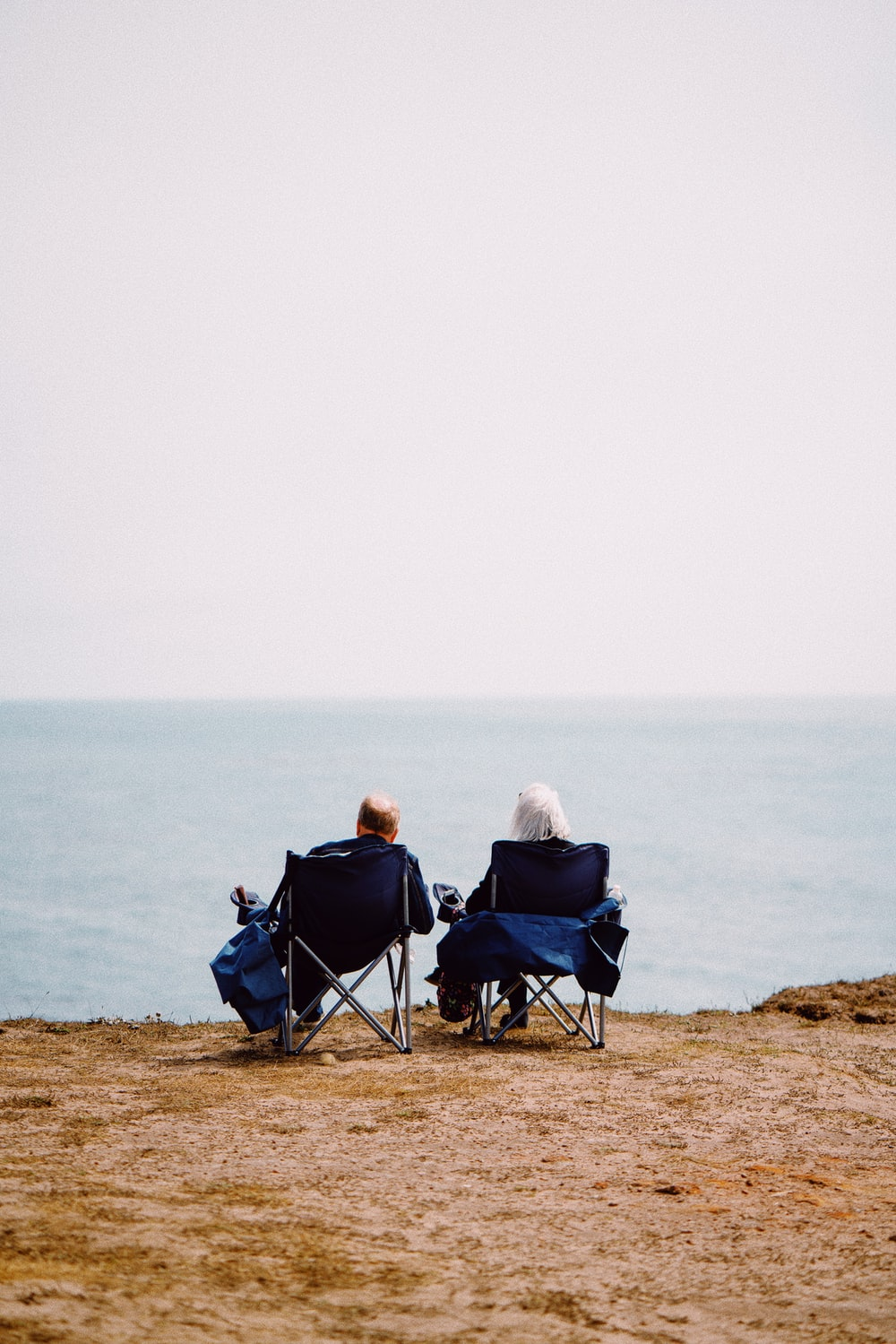 2 person sitting on blue camping chairs on brown field during daytime