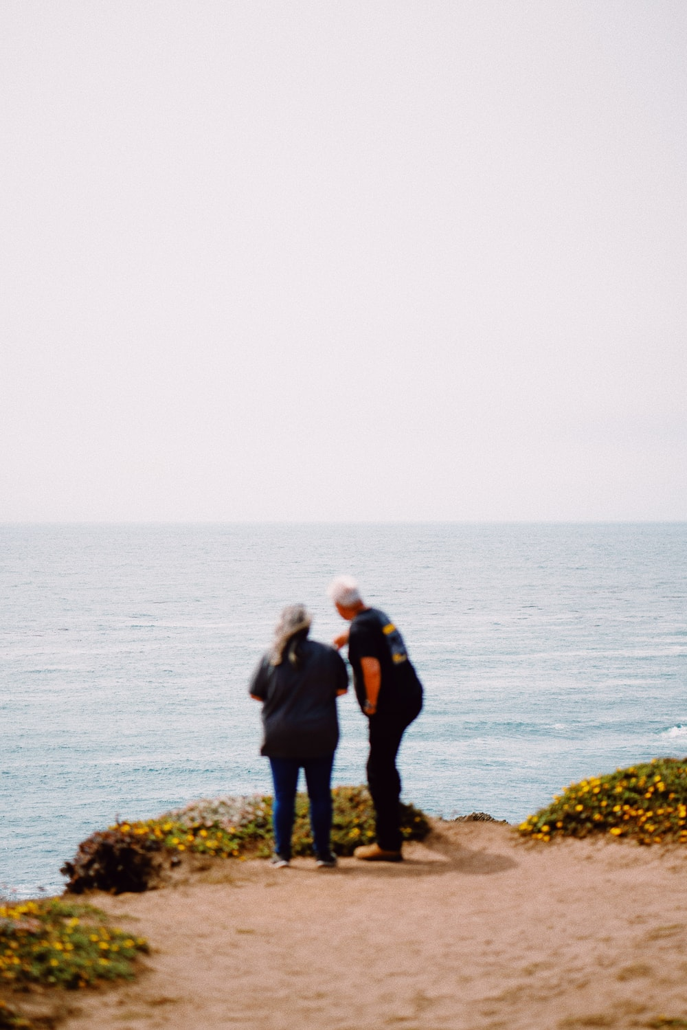 man and woman standing on rock near body of water during daytime