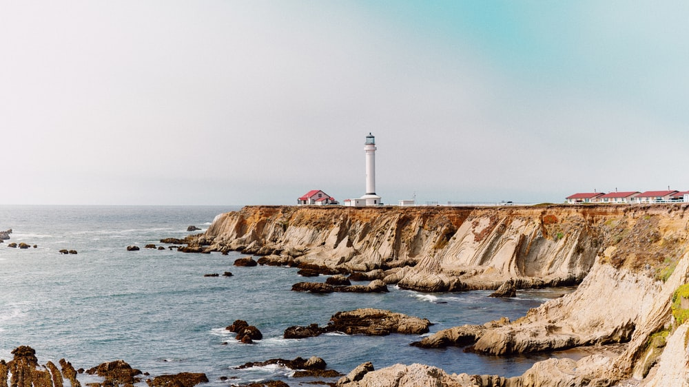 white and red lighthouse on brown rocky mountain beside sea during daytime