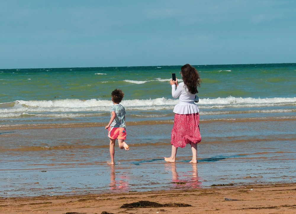 2 girls walking on beach during daytime
