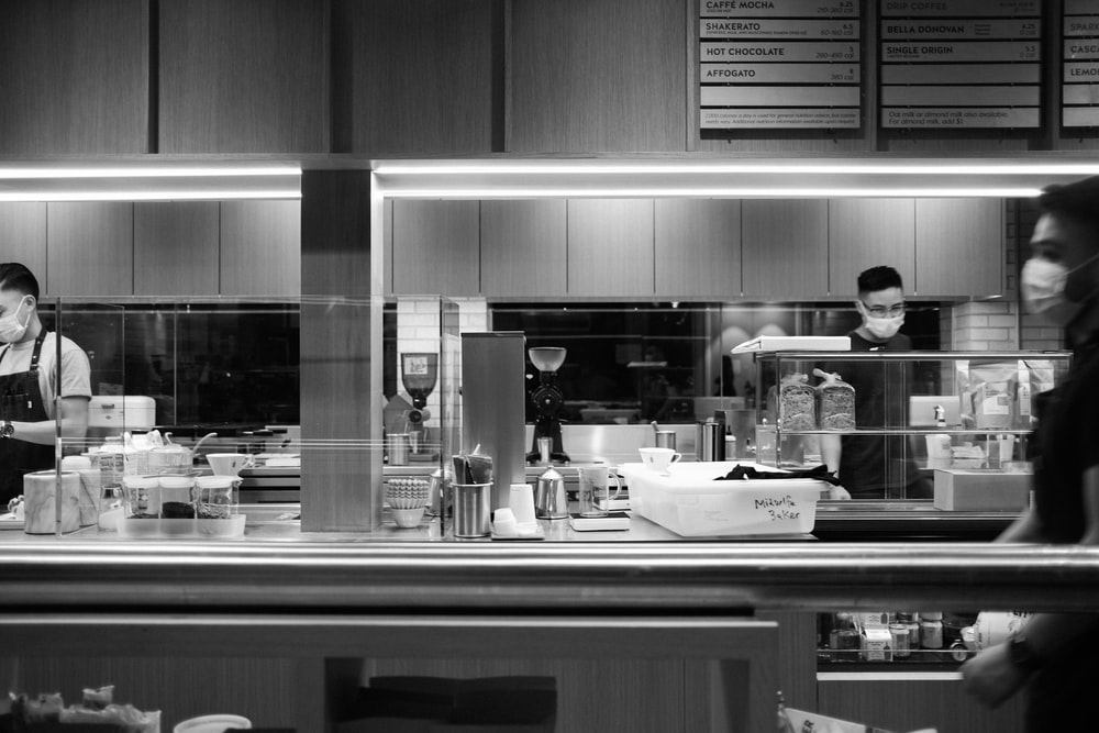 grayscale photo of man in kitchen