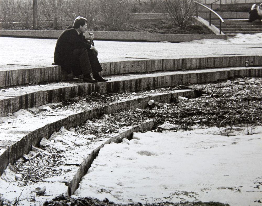 man in black jacket and black pants sitting on concrete stair during daytime
