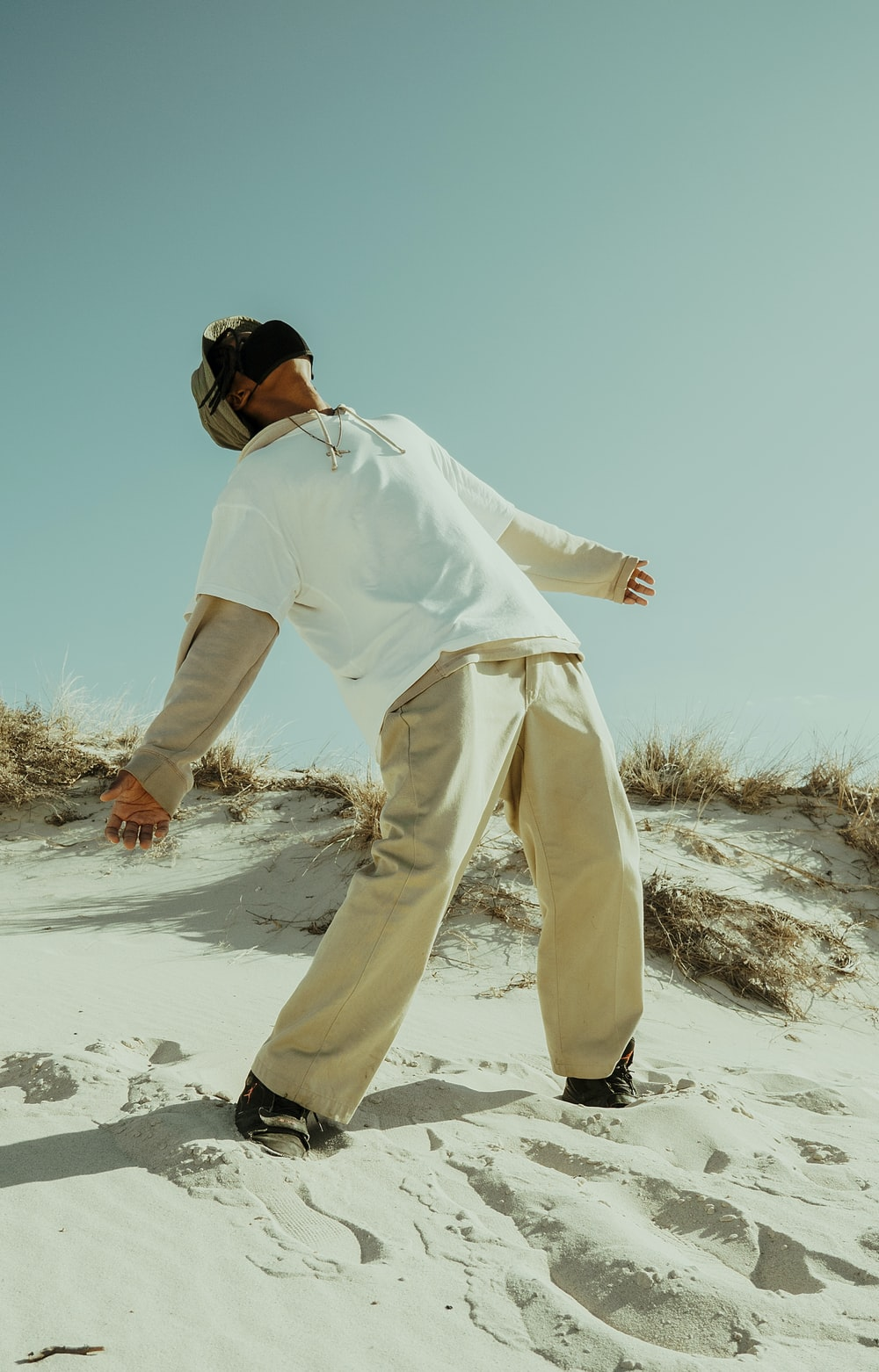 man in white long sleeve shirt and pants standing on white sand during daytime
