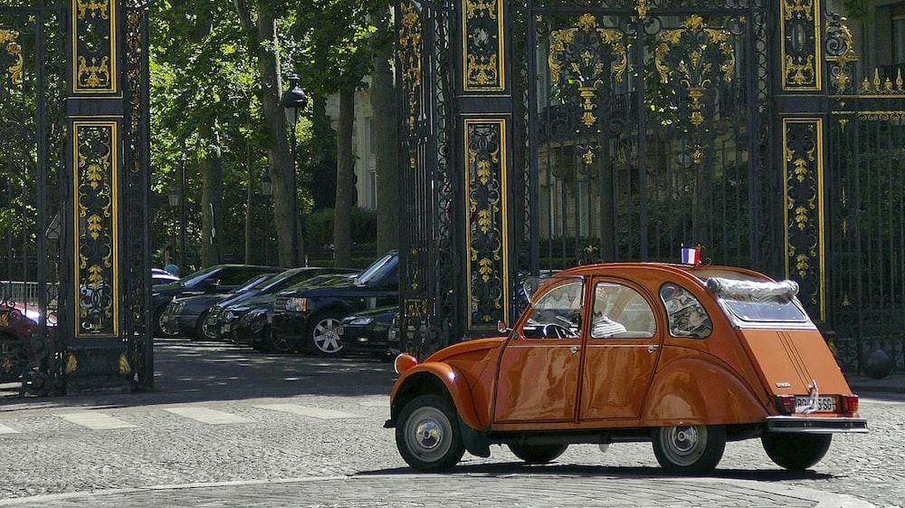 orange volkswagen beetle parked on sidewalk during daytime
