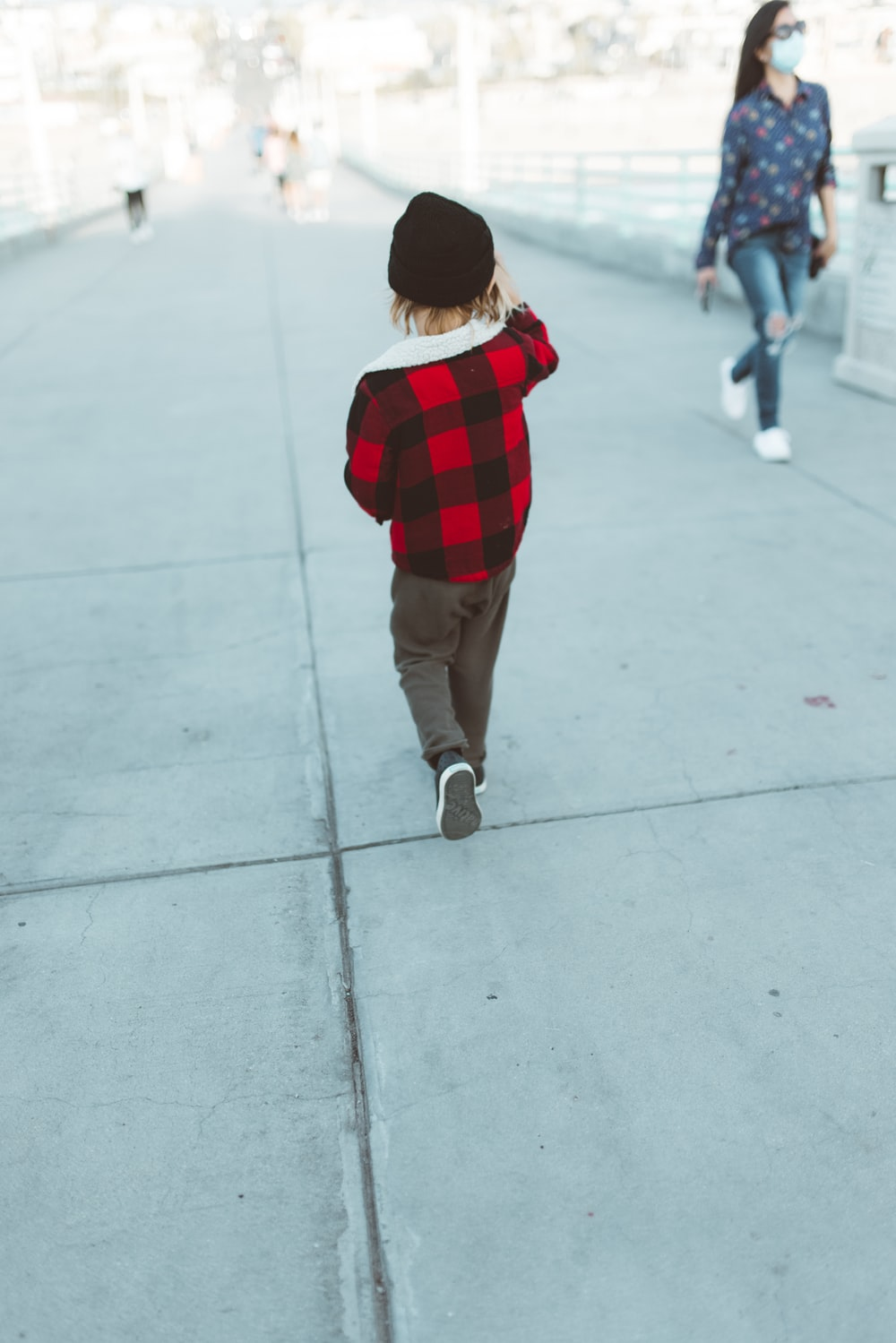 child in red and black plaid shirt and brown pants walking on gray concrete floor