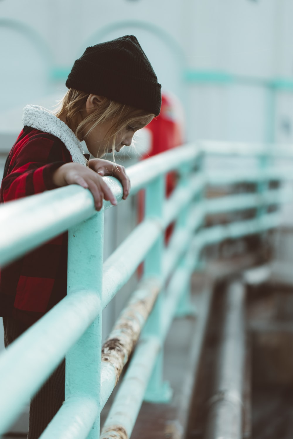 woman in red and black jacket leaning on white metal railings during daytime