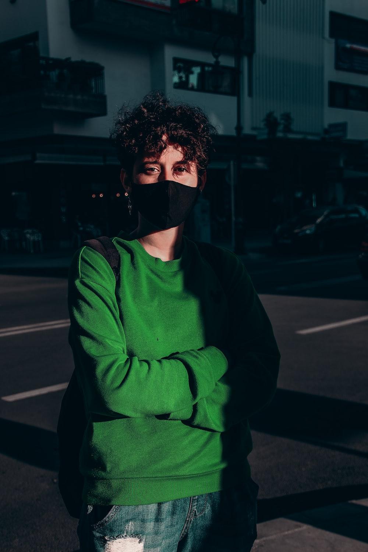man in green sweater wearing black mask standing on sidewalk during night time