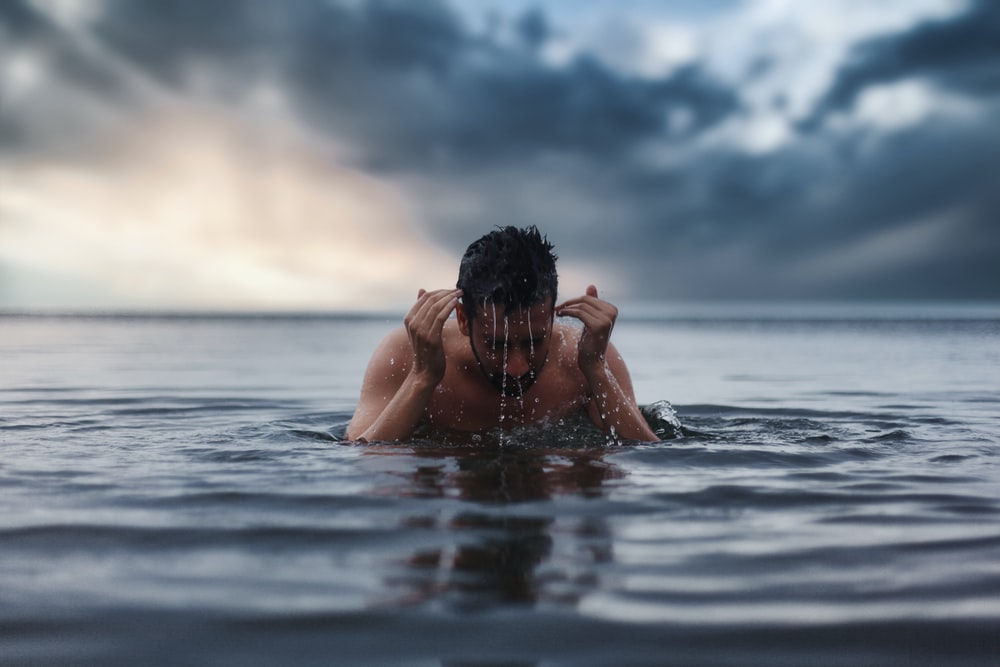 topless man in water during daytime