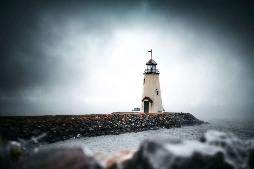 white and black lighthouse under gray sky