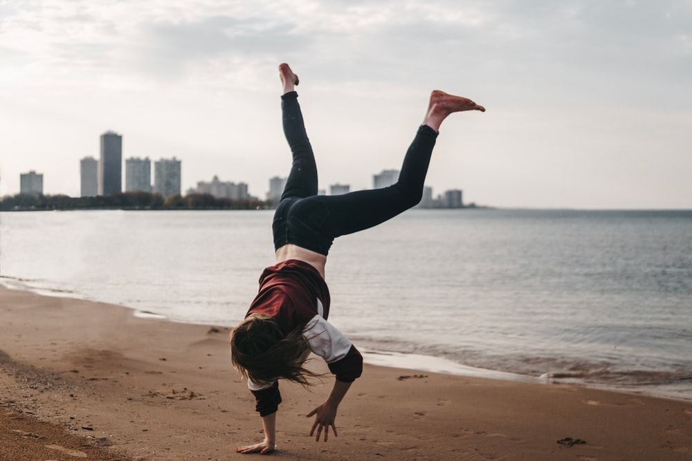 woman in black pants and white shirt jumping on beach during daytime