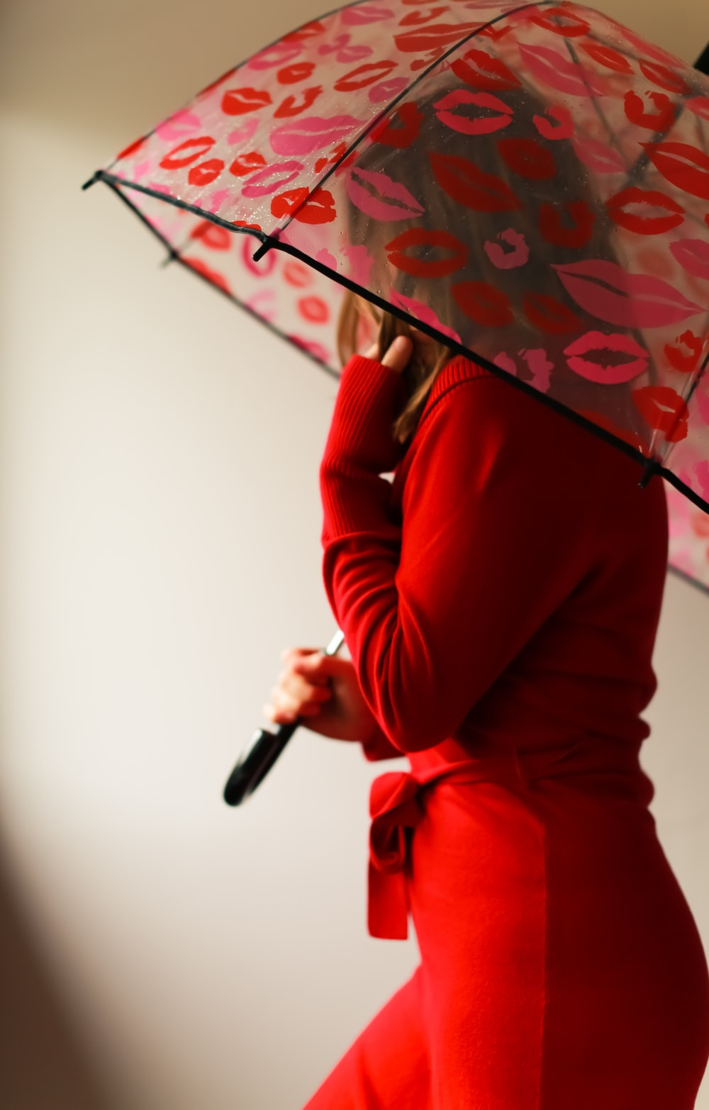 woman in red long sleeve shirt holding umbrella