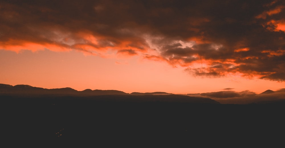 silhouette of mountain under orange and gray clouds