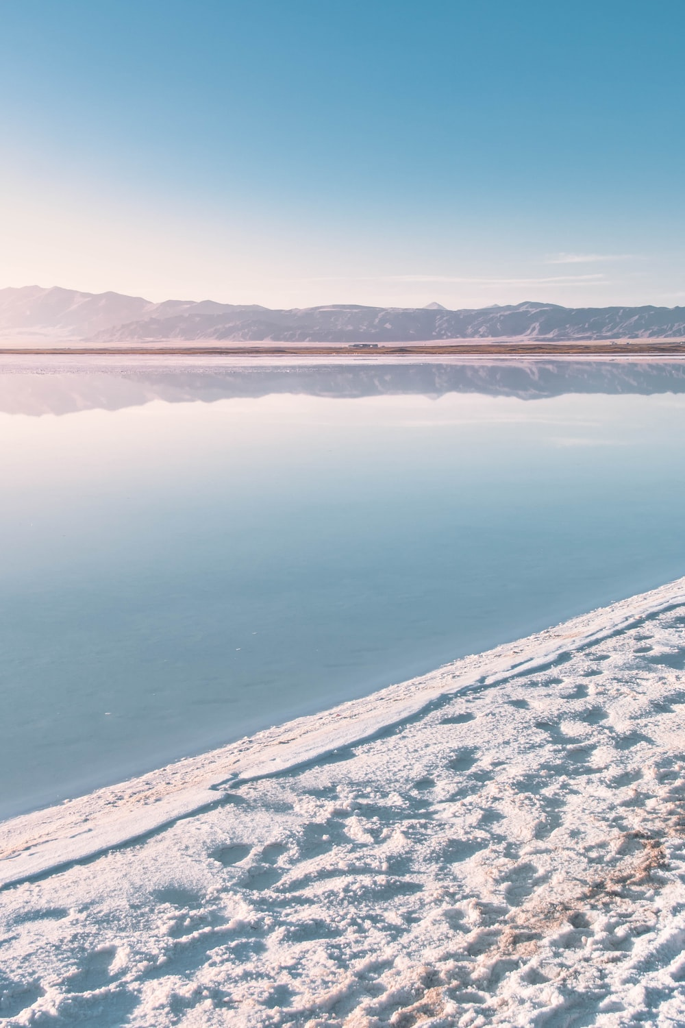 body of water near snow covered mountain during daytime