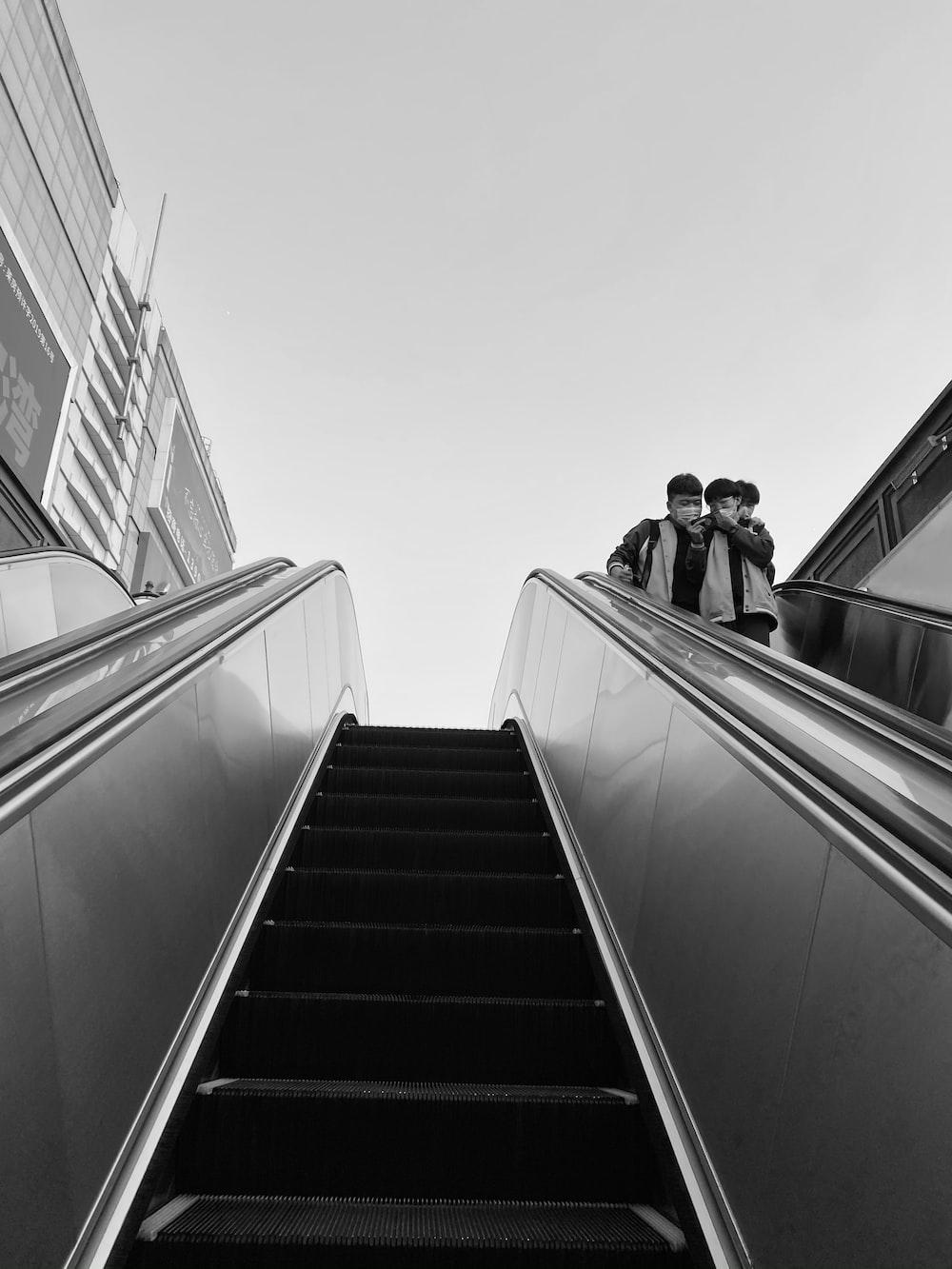 grayscale photo of 2 women on escalator
