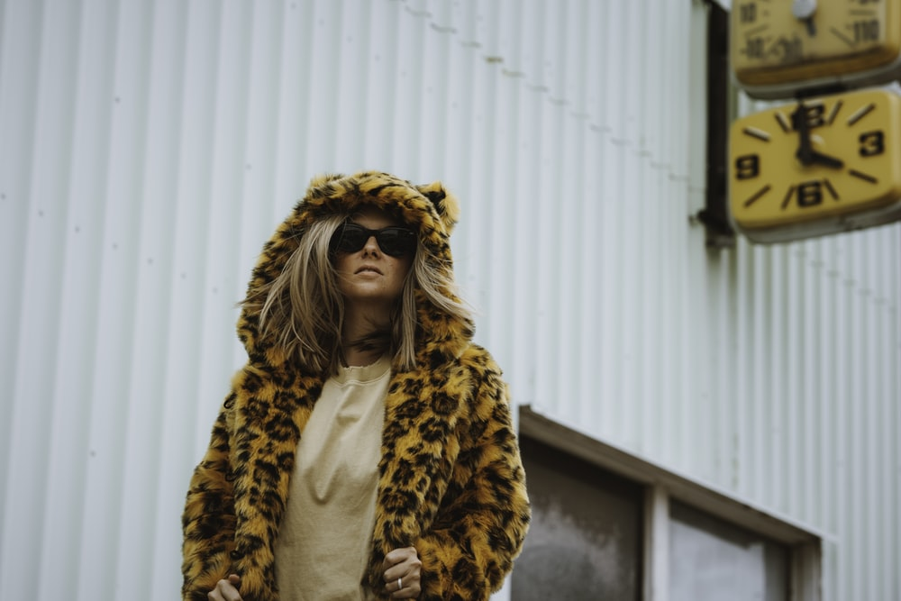 woman in brown and black leopard print coat standing near white wall during daytime