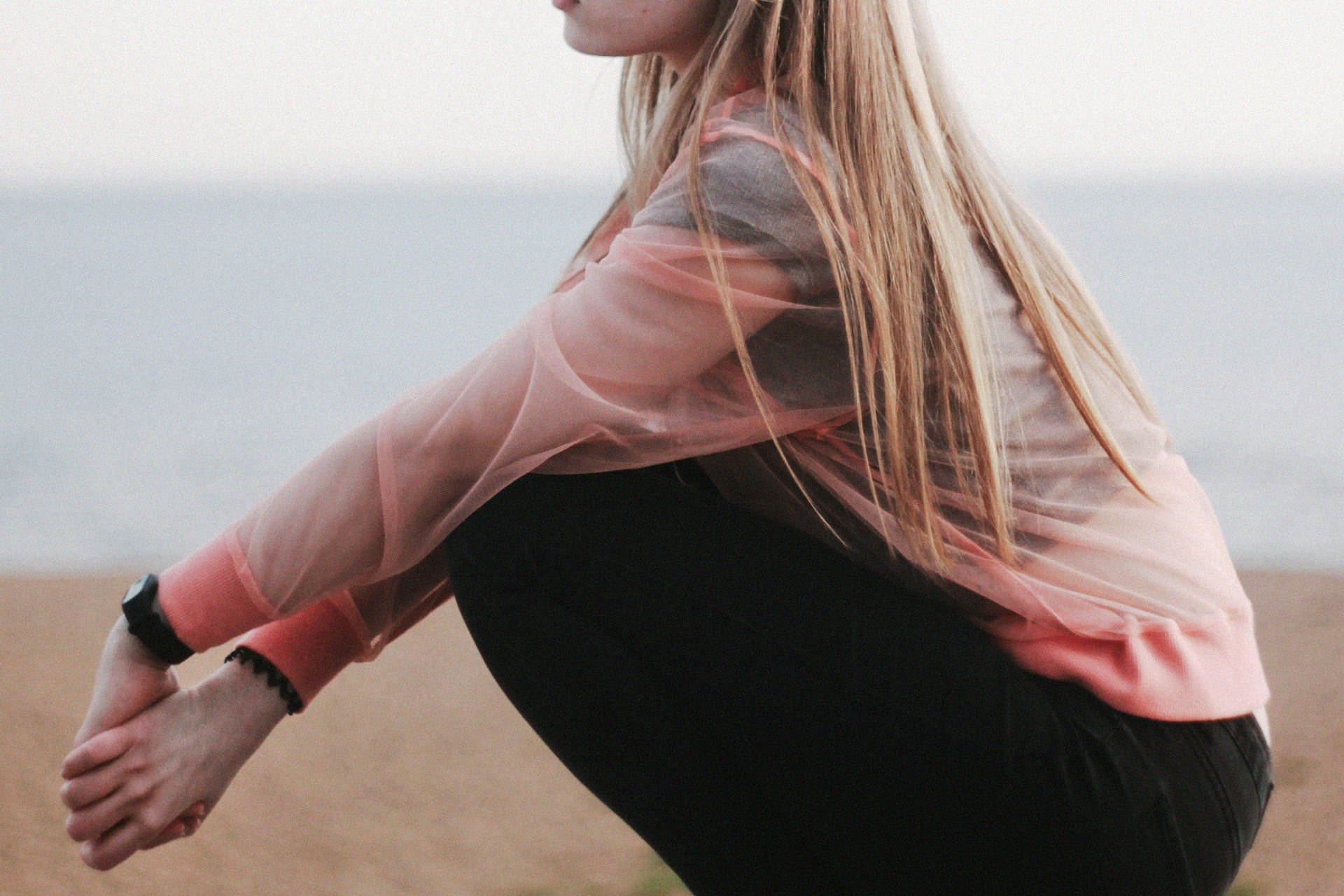 woman in pink long sleeve shirt and black pants sitting on brown sand during daytime
