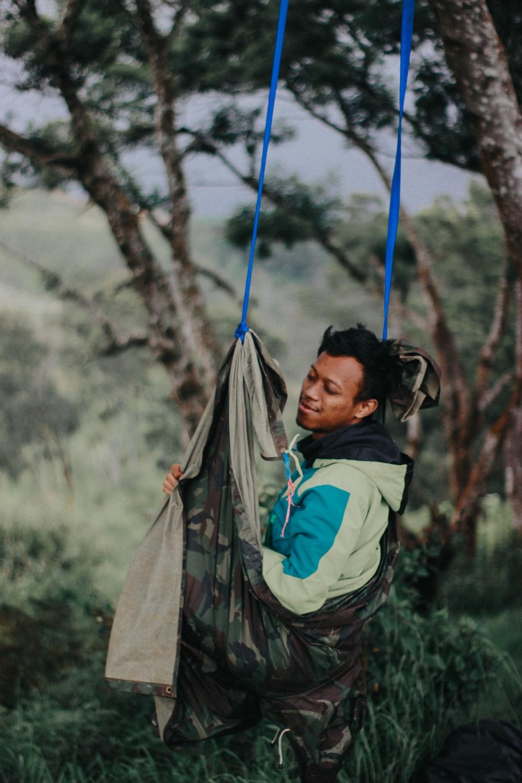 woman in green jacket sitting on hammock