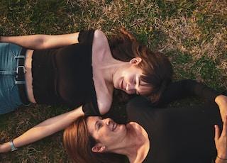 woman in black sleeveless dress lying on green grass field