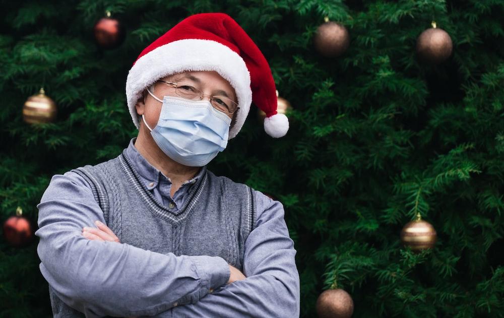 man in gray sweater wearing santa hat
