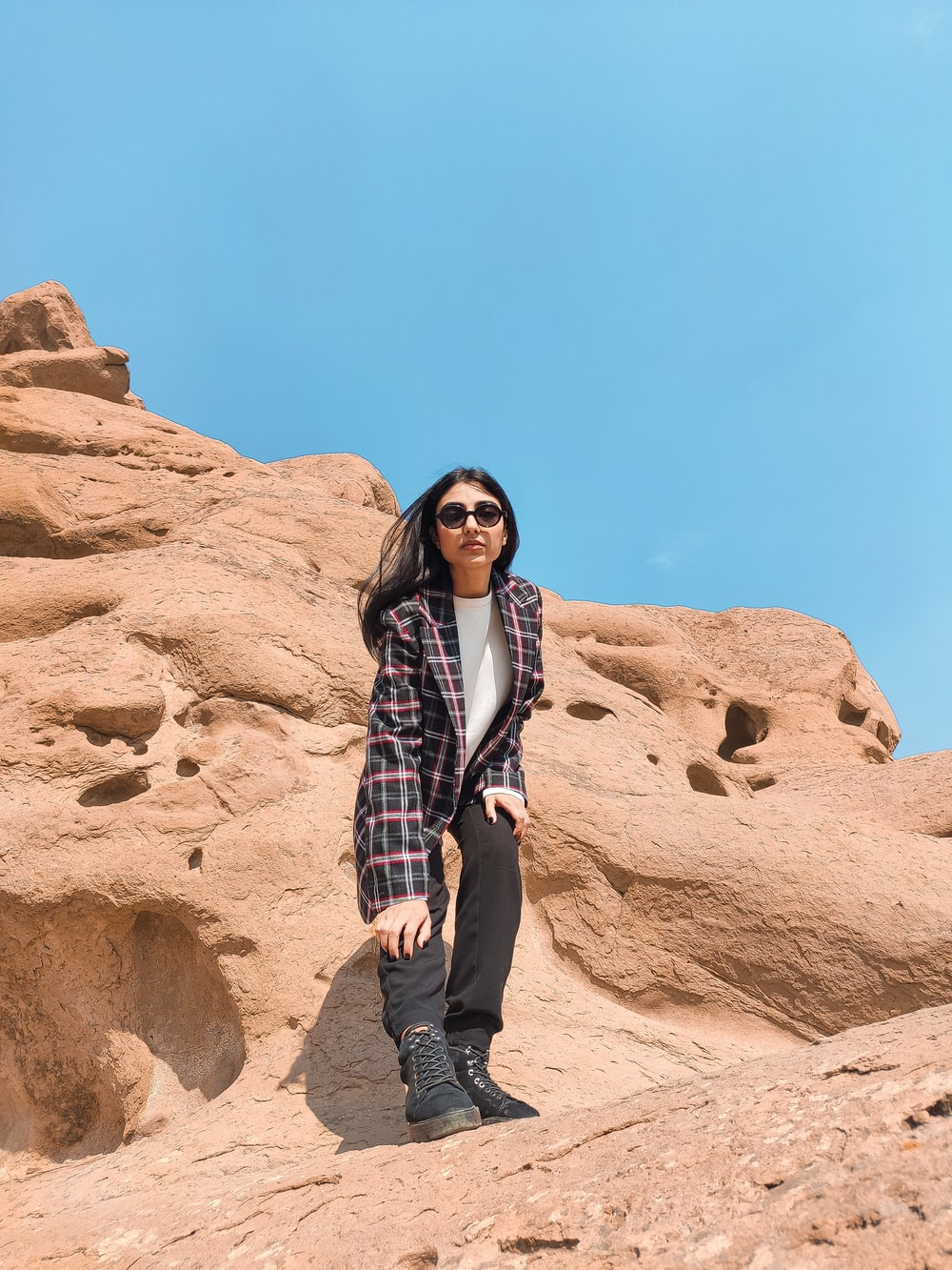 woman in black and white plaid dress shirt standing on brown rock formation during daytime