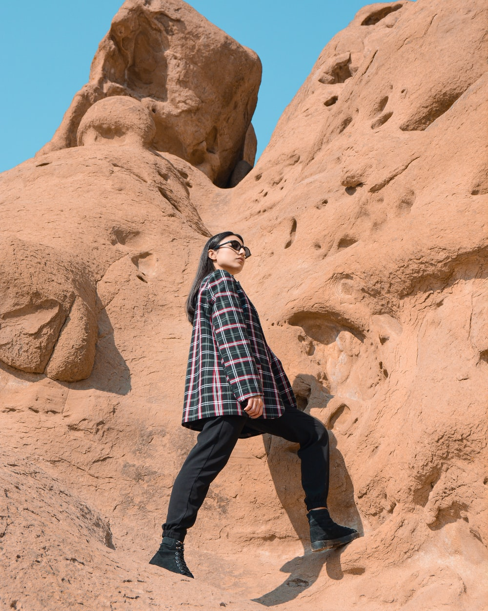 man in blue and white plaid dress shirt and black pants standing on brown rock formation