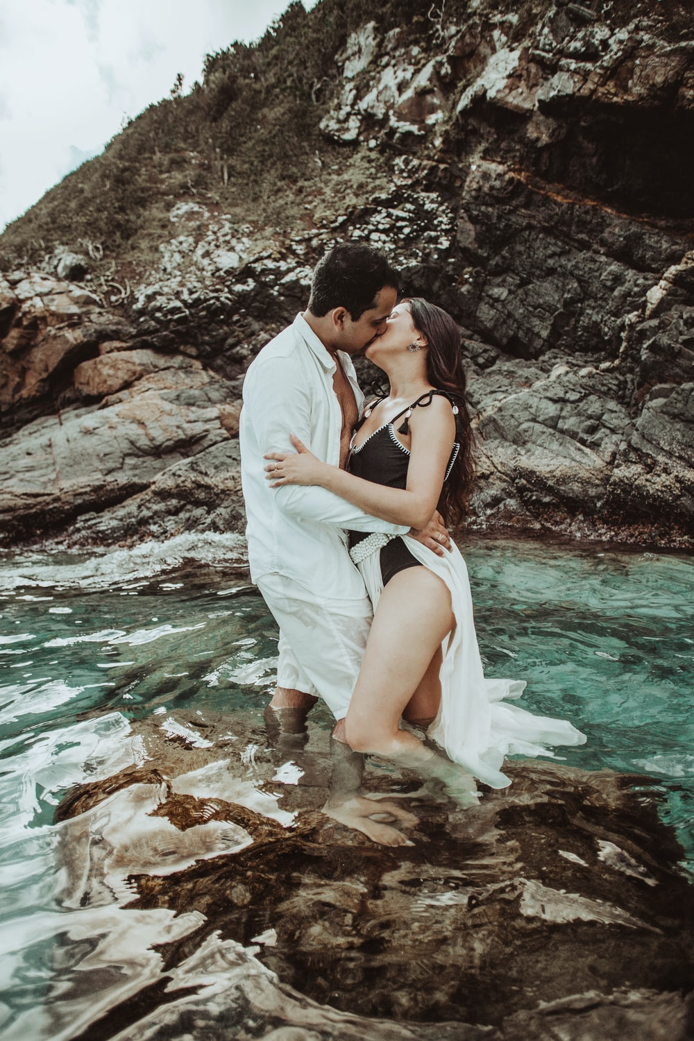 couple kissing on rocky shore during daytime