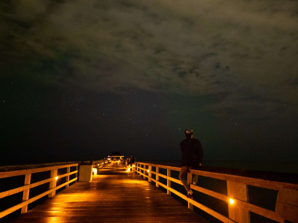 man in black jacket standing on brown wooden dock during night time