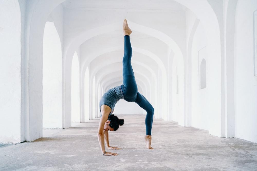 woman in blue leggings and black tank top doing yoga