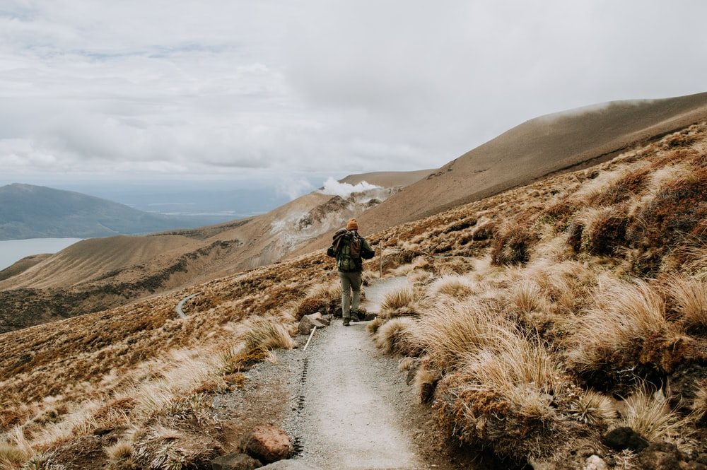 people walking on pathway near brown mountain under white clouds during daytime