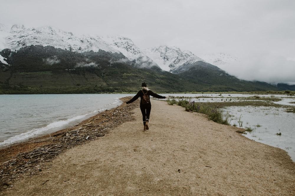 woman in black long sleeve shirt and black pants walking on brown dirt road near lake