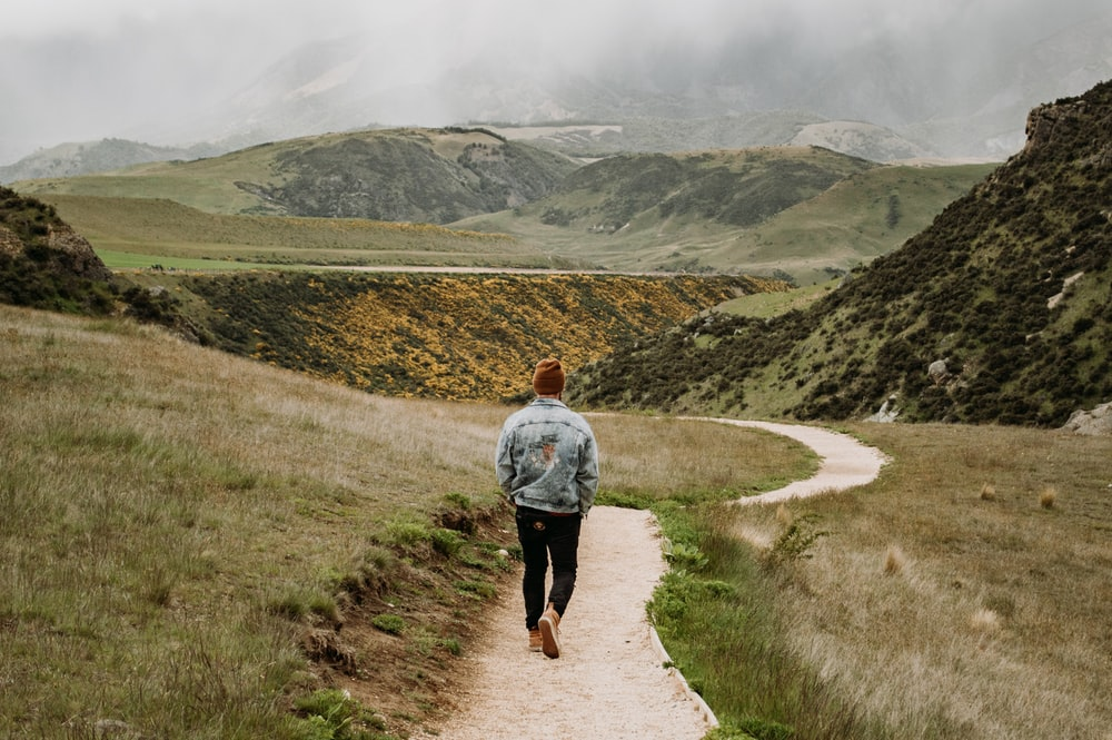 man in gray shirt walking on pathway